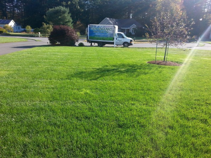 This Is A Photo Of A New England Lawn Care Truck At A Residence Doing A Seeding On A Large Front Lawn