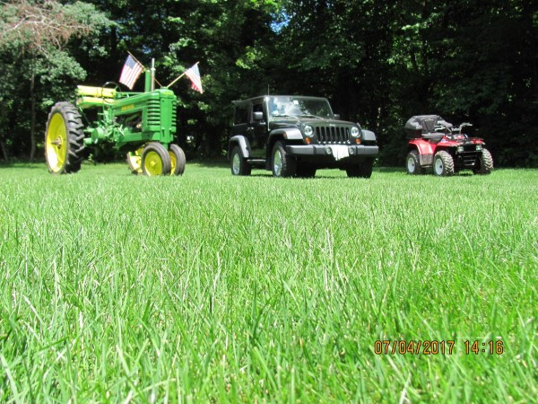 This Is A Photo Of A Lawn In Southwick Ma With A Tractor, A Jeep And A Riding Lawnmower Side By Side