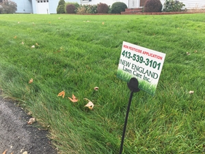 photo of a new england lawn care sign posted in front of suburban home, new england lawn care, western ma